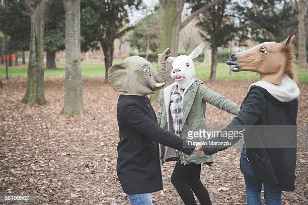 three sisters wearing animal masks dancing in park - rabbit mask stock pictures, royalty-free photos & images