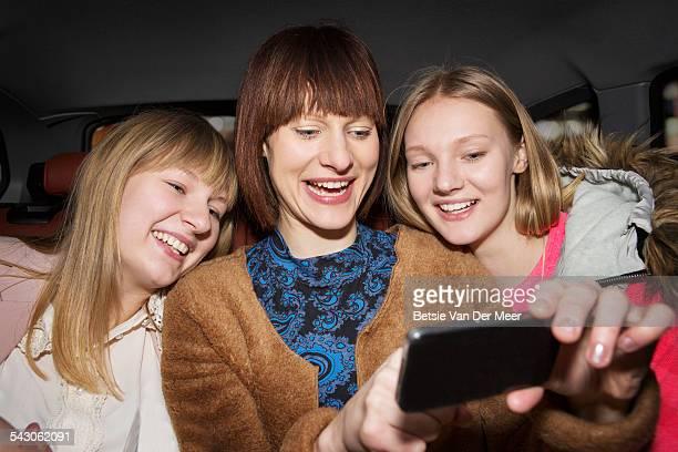 Three sisterstaking Selfie in cab at night.