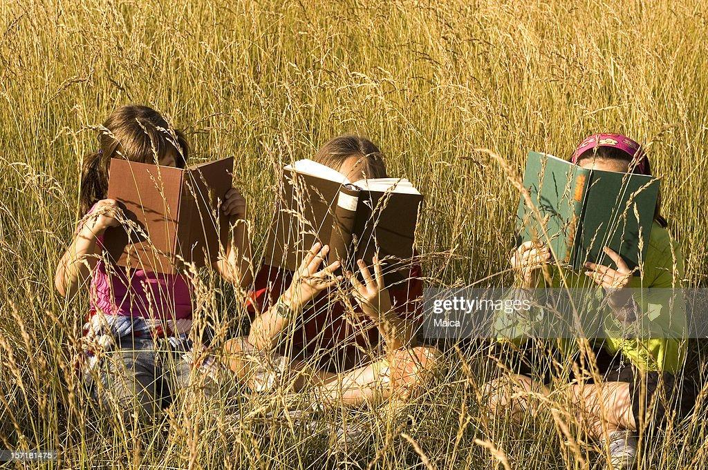 Three sitting and reading : Stock Photo