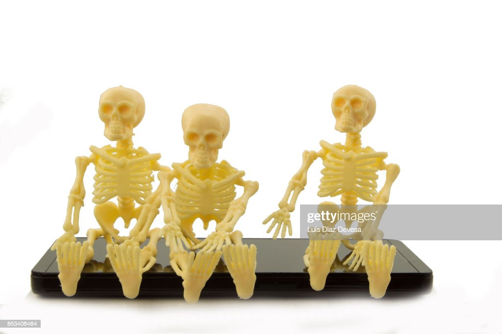 Three skeletons sat in a Mobile phones : ストックフォト
