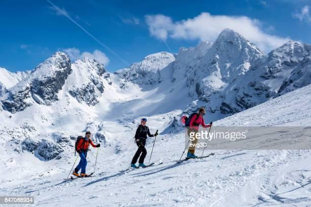 Three skiers go uphill on the ski slope, Tatra Mountains