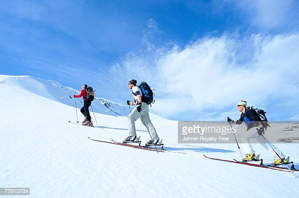 Three skiers going up the ski slope Storulvan Jamtland Sweden.