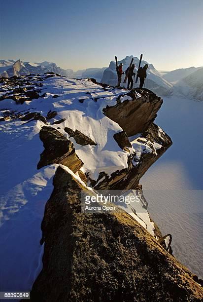3 つのスキーヤーの崖の上に立つエッジ外 - バフィン島 ストックフォトと画像