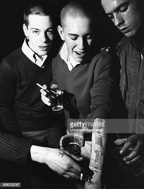 Three skinheads drinking showing a 'Kill Mods' tatoo UK 1980's