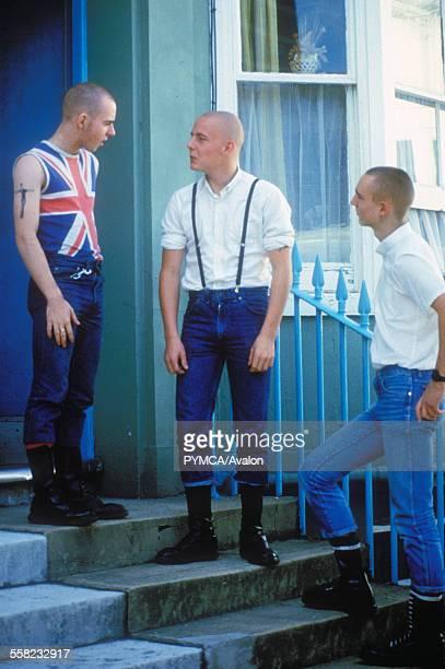 Three skinheads having a chat on the doorsteps, Brighton, UK 1980's.