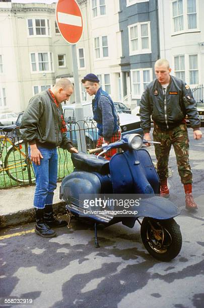 Three skinheads looking very shifty around a parked scooter Brighton UK 1980's