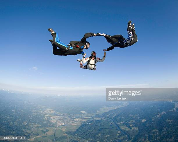 three skydivers holding hands during freefall, aerial view - drei personen stock-fotos und bilder