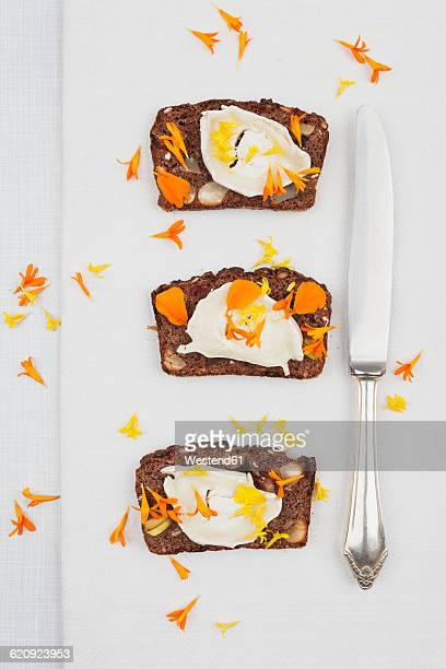 Three slices of home-baked ginger bread with cream cheese and petals of marigold