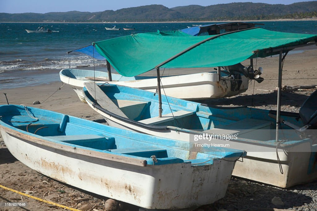 Three small boats with shade cloths on a beach, others moored in the ocean on Tenacatita Bay, Costalegre, Jalisco, Mexico : Stock Photo