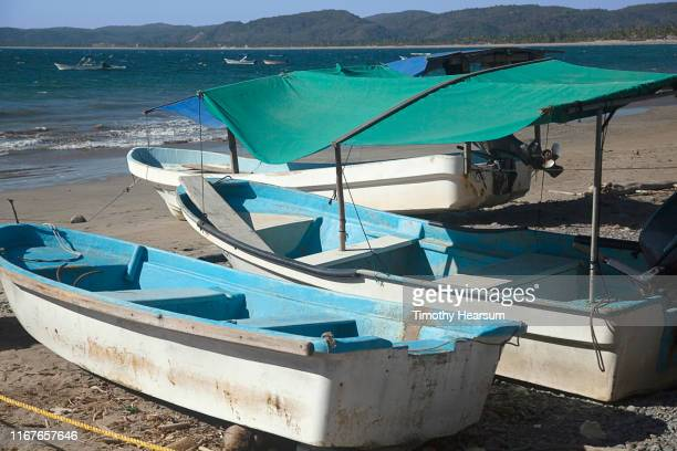 three small boats with shade cloths on a beach, others moored in the ocean on tenacatita bay, costalegre, jalisco, mexico - timothy hearsum stock-fotos und bilder