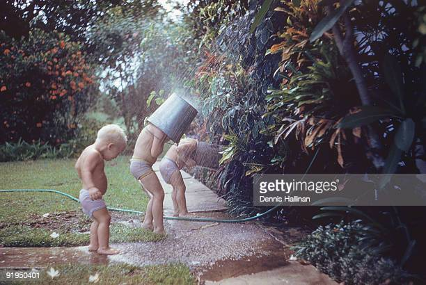 Three small boys playing in outdoor shower