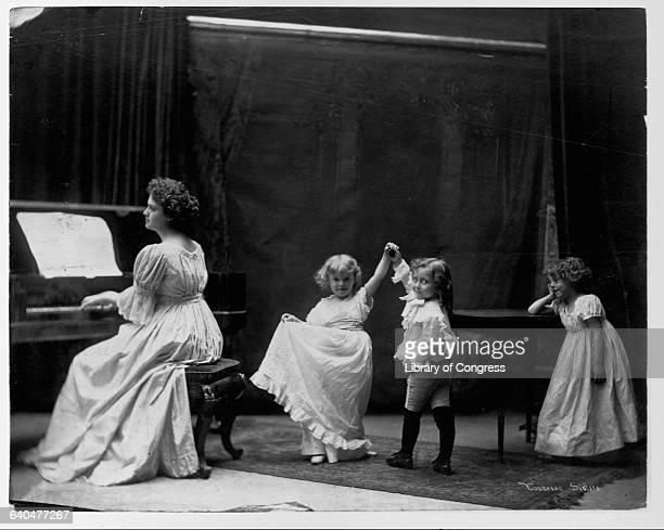 Three small children dance playfully as a woman plays the piano