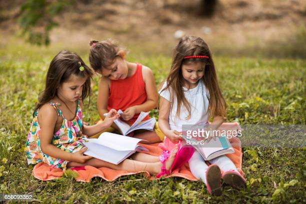 three small girls reading books in the park. - in the park day 3 imagens e fotografias de stock