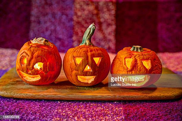 three small jack-o-lanterns - ugly pumpkins stock photos and pictures