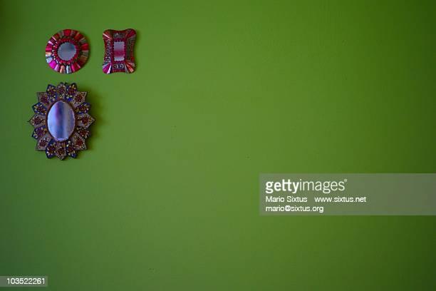 Three small mirrors at an ampty green wall