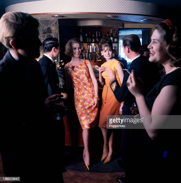 Three smartly dressed couples socialising at a cocktail lounge circa 1963