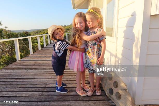 three smartly dressed kids embracing - first occurrence photos et images de collection