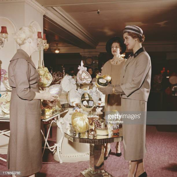 Three smartly dressed women peruse a selection of chocolate easter eggs on a display stand at the Fortnum Mason grocery store in London in April 1958