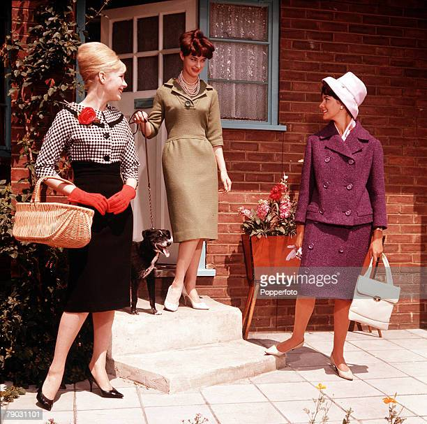 Three smartly dressed women step out of the house for a summer stroll with their shopping bags and a dog One woman carries a basket and is wearing an...