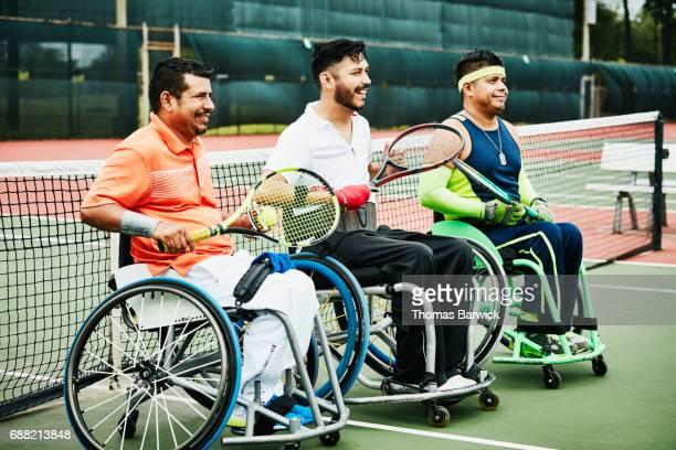 three smiling adaptive athletes at net after wheelchair tennis match - 車いすテニス ストックフォトと画像