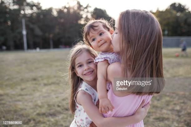 three smiling beautiful sisters hugging - sibling stock pictures, royalty-free photos & images