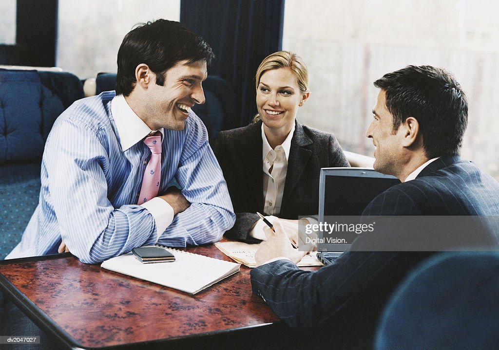 Three Smiling Business Executives Having a Discussion on a Passenger Train : Stock Photo