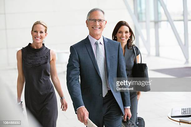 three smiling business people walking together at office lobby - compleet pak stockfoto's en -beelden