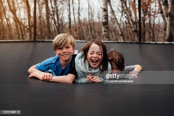 three smiling children lying on a trampoline in the garden, usa - children only stock pictures, royalty-free photos & images