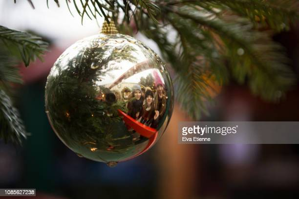 Three smiling girls reflected in a shiny Christmas bauble on a tree at a Christmas market