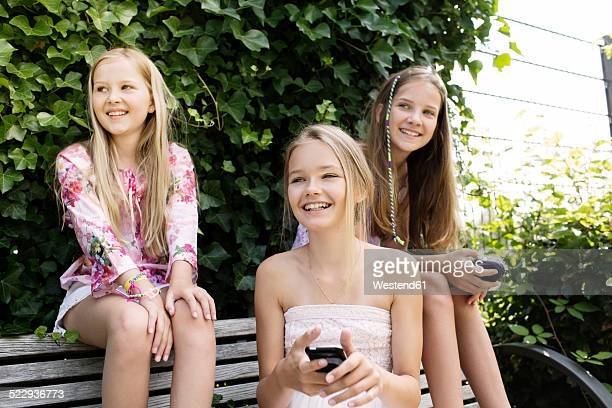 Three smiling girls sitting on a park bench