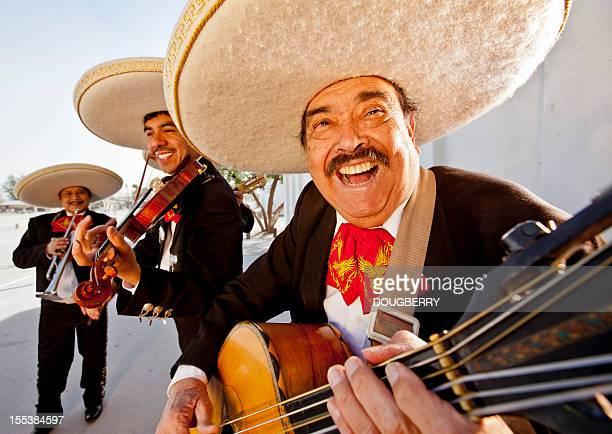 tres sonriendo miembros de una banda mariachi - mariachi fotografías e imágenes de stock