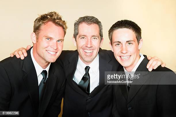Drei lächelnde Männer in schwarzen Anzügen Porträt