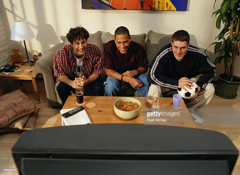 Three Smiling Men Watching Television : Stock Photo