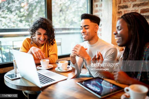 Three smiling millennials working from the bar.