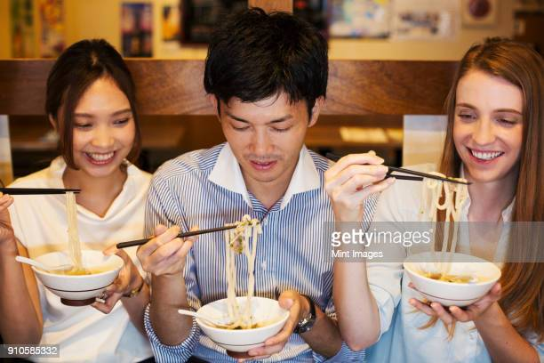 Three smiling people sitting side by side at a table in a restaurant, eating from bowls using chopsticks.