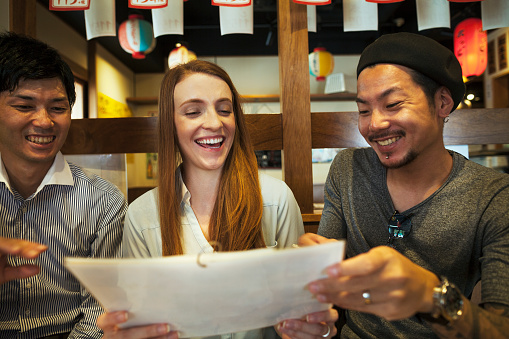 Three smiling people, woman and two men, sitting side by side at a table in a restaurant, looking at menu. - gettyimageskorea