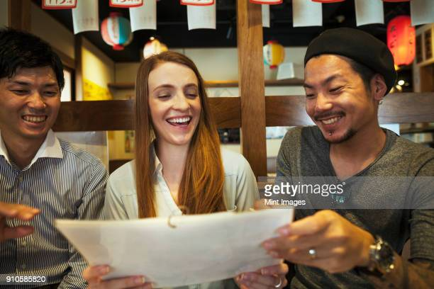 Three smiling people, woman and two men, sitting side by side at a table in a restaurant, looking at menu.