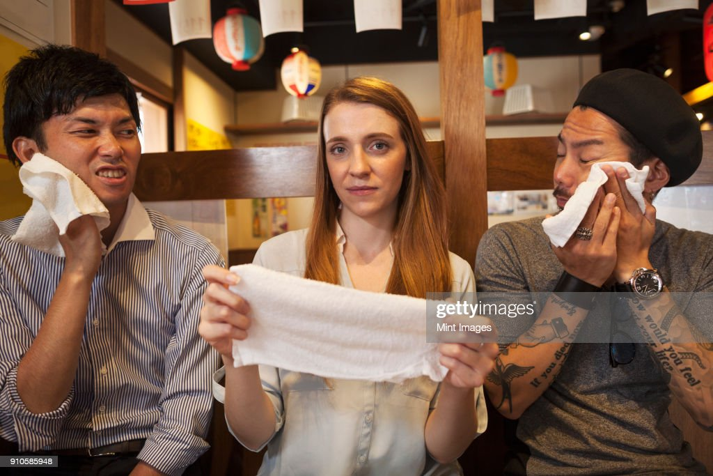 Three smiling people, woman and two men, sitting side by side at a table in a restaurant, holding wet towels. : ストックフォト