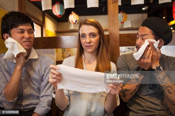 Three smiling people, woman and two men, sitting side by side at a table in a restaurant, holding wet towels.
