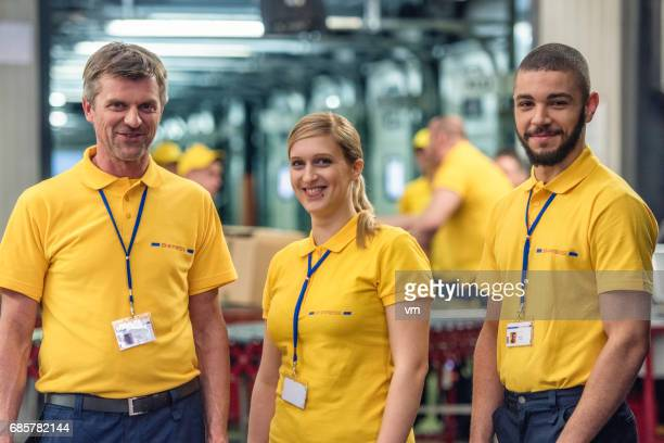 three smiling postal workers looking at camera - carteiro imagens e fotografias de stock