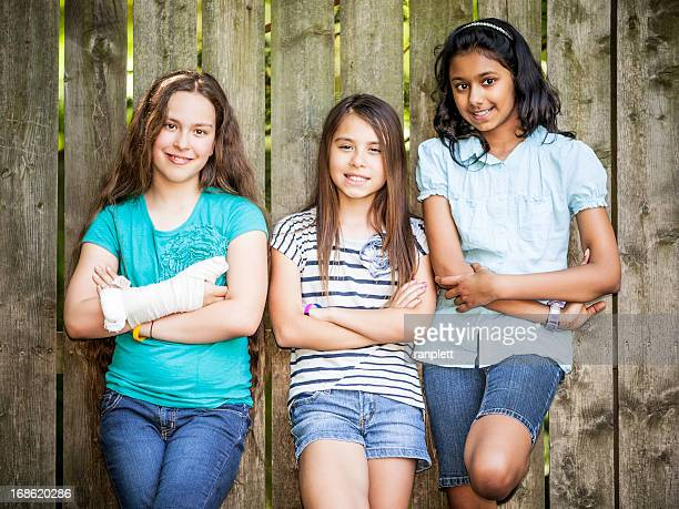 Three smiling Pre-Teen Girls Leaning Against a Fence