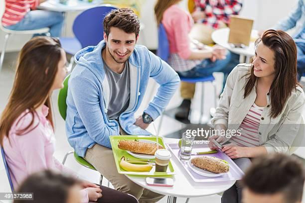 Trois étudiants souriants parlant lors d'une pause déjeuner.
