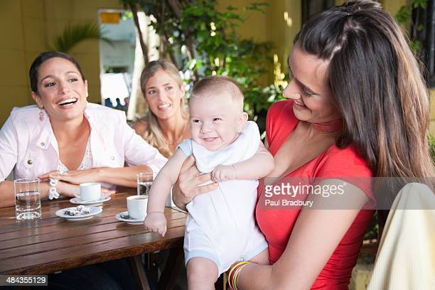three smiling woman on outdoor patio where one is holding a baby - birthing chair stock pictures, royalty-free photos & images