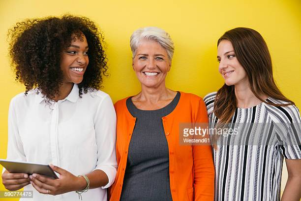 three smiling women standing in front of a yellow wall - tres personas fotografías e imágenes de stock