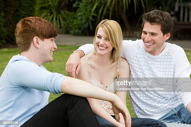 """three smiling young adults sitting outdoors - """"compassionate eye"""" stock pictures, royalty-free photos & images"""