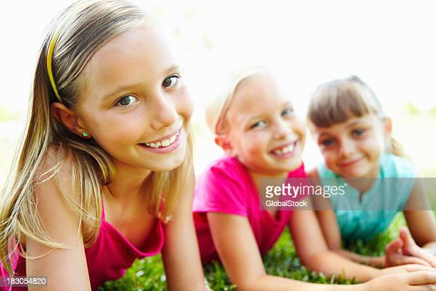 three smiling young friends lying on grass - young tiny girls stock photos and pictures