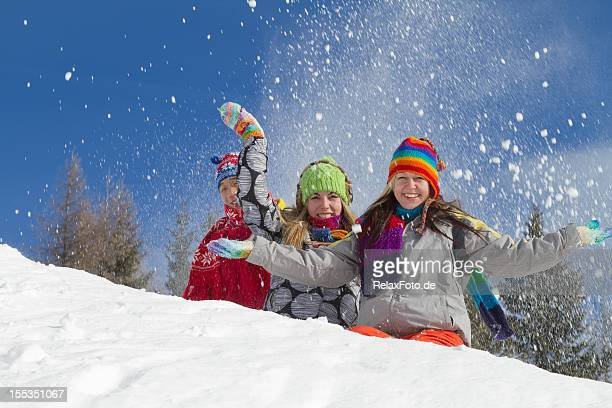 Three smiling young people in winter clothes sitting on snow