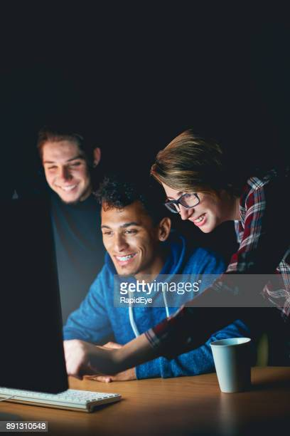 Three smiling young people study computer monitor at night