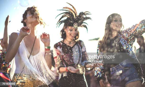 Three smiling young women at a summer music festival face painted, wearing feather headdress, dancing among the crowd.