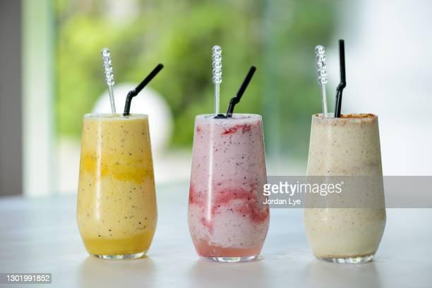 three smoothies on a table - トロピカルフルーツ ストックフォトと画像